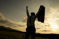 Silhouette of a businessman raising his arm