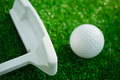 Golf ball with putter on green course. Selective focus - PhotoDune Item for Sale