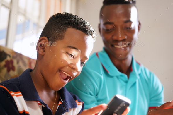 Father Teaching Mobile Telephone Technology To Son At Home - Stock Photo - Images