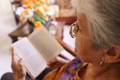 Old Lady Reading Book On Armchair In Hospice