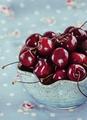 Red cherries in blue ceramic bowl