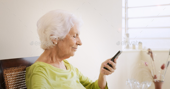 Happy Old Woman Using Mobile Phone For Leisure