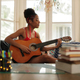 Mixed Race Girl Singing And Playing Classic Guitar At Home - PhotoDune Item for Sale