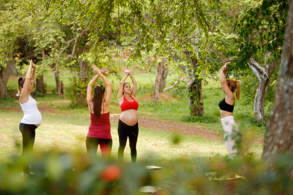 Pregnant Women Doing Yoga With Personal Trainer In Park - Stock Photo - Images