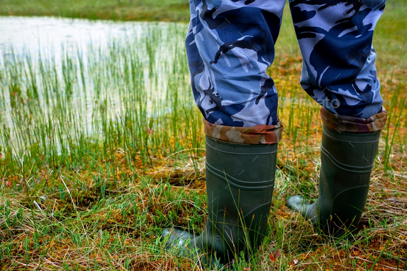 A man in rubber wool boots stands moss at the edge of the lake.