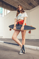 young youth female with skateboard on street