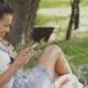 Content Girl Using Smartphone in Park - VideoHive Item for Sale