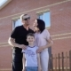 Happy Family Standing Near Their House in Sunny Summer Day Embracing Each Other