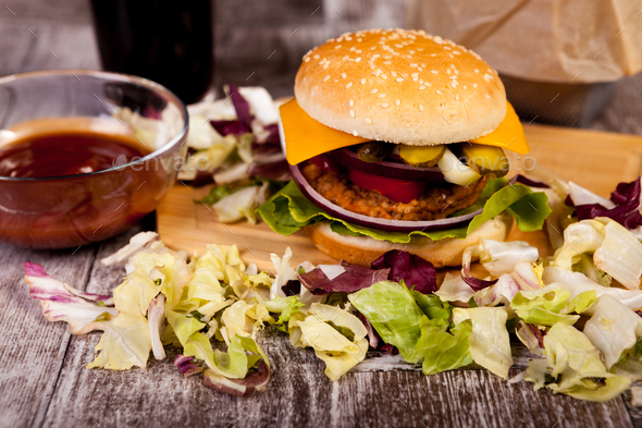 Delicious home made burgers on wooden plate next to fries and co - Stock Photo - Images