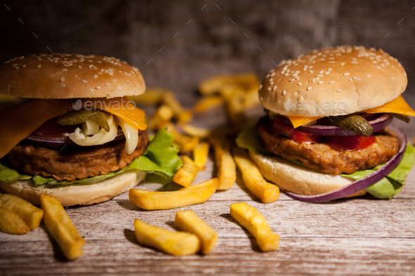 Tasty burgers on wooden plate - Stock Photo - Images
