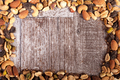 Mix of healthy raw nuts on wooden background with copyspace avai