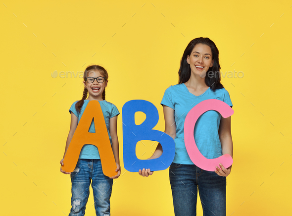 child and teacher with big letters