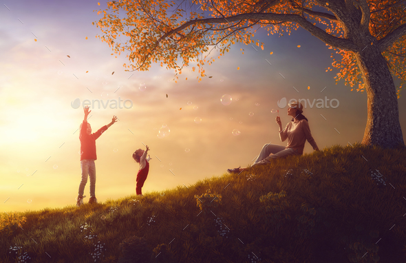 Mother and children playing on autumn walk