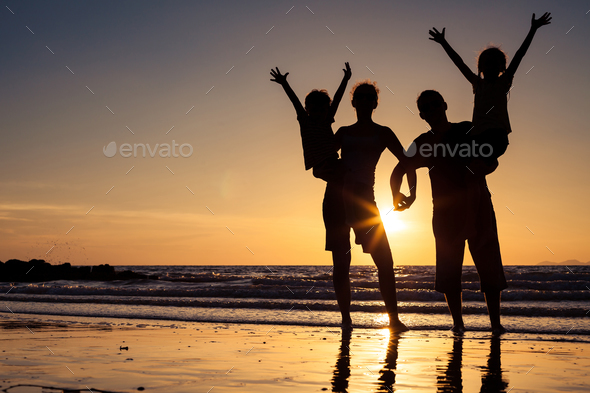 Silhouette of happy family who standing on the beach at the suns - Stock Photo - Images
