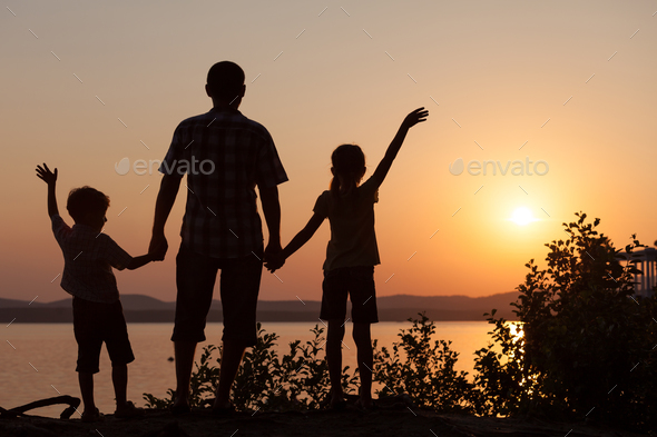 father and children playing on the coast of lake