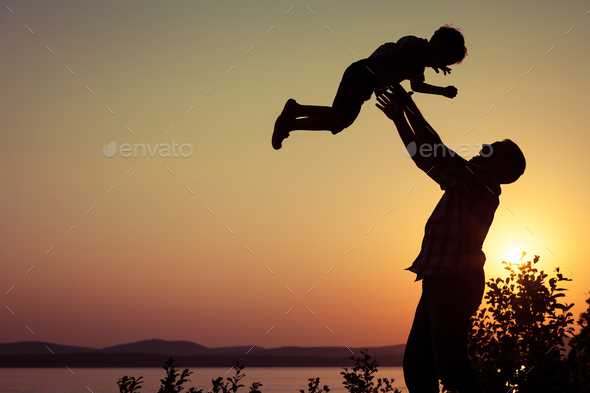 father and son playing on the coast of lake - Stock Photo - Images