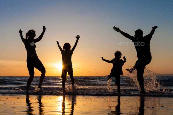Silhouette of happy family who playing on the beach at the sunse - Stock Photo - Images