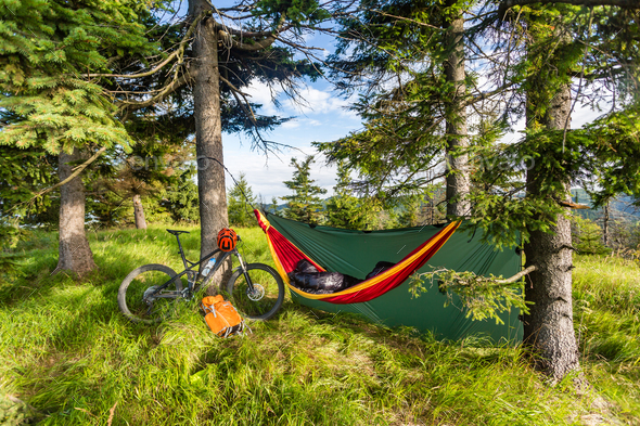 Camping with hammock  in summer woods on bike travel