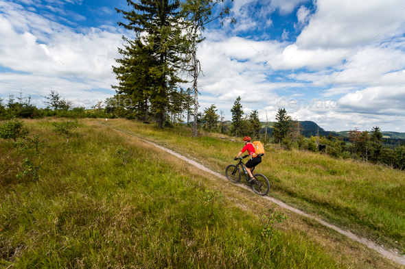 Rider on Mountain Bike riding in woods and mountains