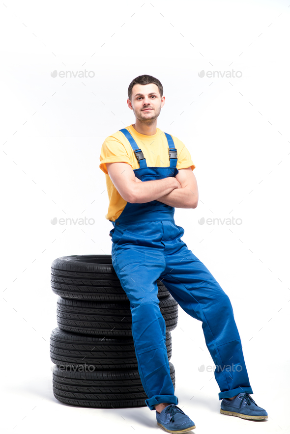 Serviceman sitting on tires, white background - Stock Photo - Images