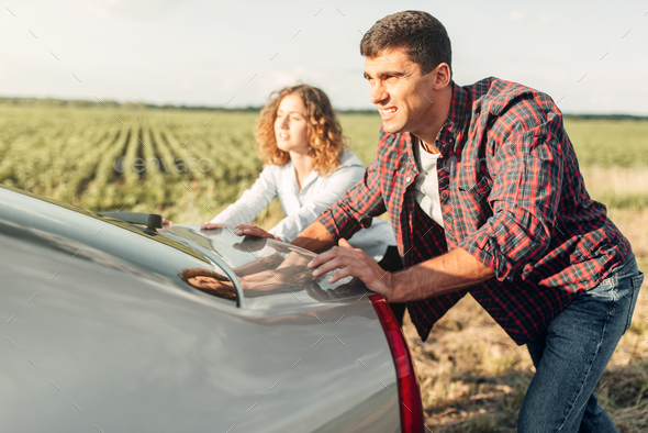 Man and woman pushing a broken car, back view - Stock Photo - Images
