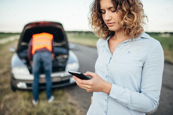 Woman calls to service, man repair broken car - Stock Photo - Images