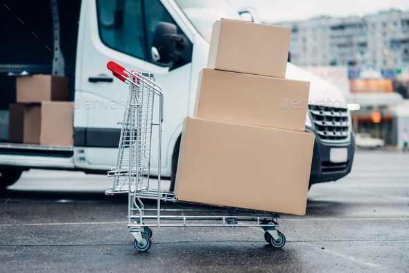 Trolley with boxes against truck, male logistic - Stock Photo - Images