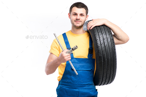 Service worker in blue uniform holds tire in hand - Stock Photo - Images