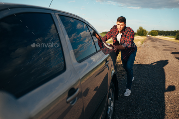 Man pushing broken car, vehicle with trounble - Stock Photo - Images