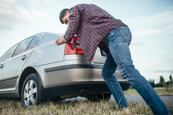 Man pushing broken car, side view - Stock Photo - Images