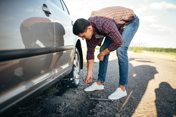 Man jack up broken car, wheel replacement - Stock Photo - Images