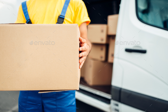 Male person in uniform holds cardboard box - Stock Photo - Images