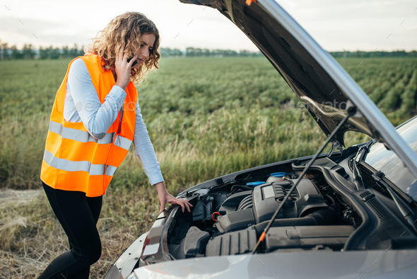Girl in reflecting vest with phone, broken car - Stock Photo - Images