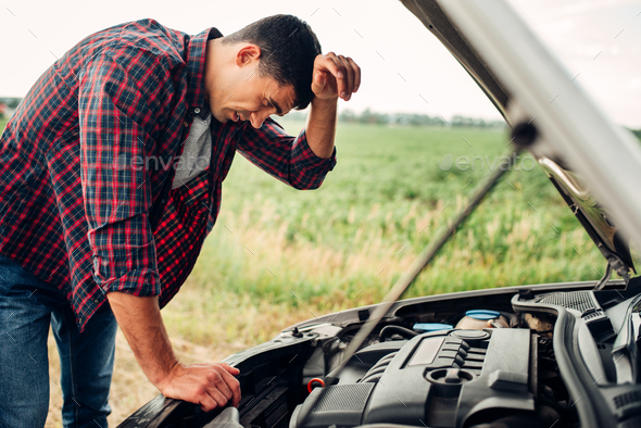 Tired man tries to repair a broken car - Stock Photo - Images