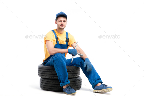 Car tire service, worker sitting on car tyres - Stock Photo - Images