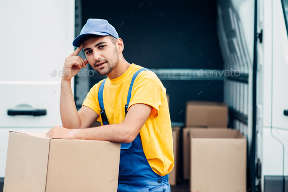Workman or courier holds carton box in hands - Stock Photo - Images