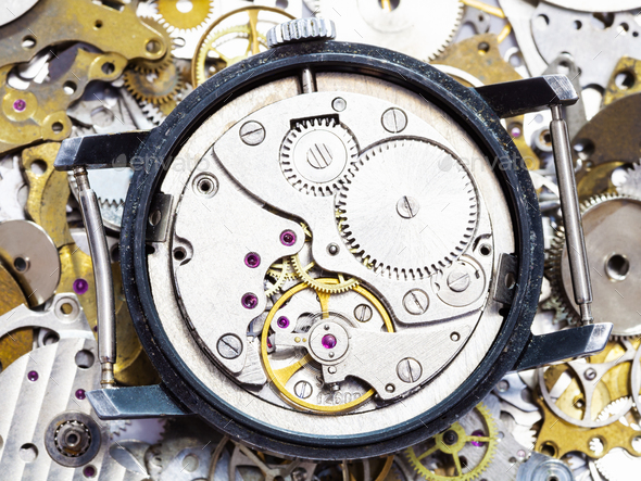 open mechanical wristwatch on pile of spare parts - Stock Photo - Images