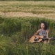 Pretty Girl Playing Guitar at Wheat Field