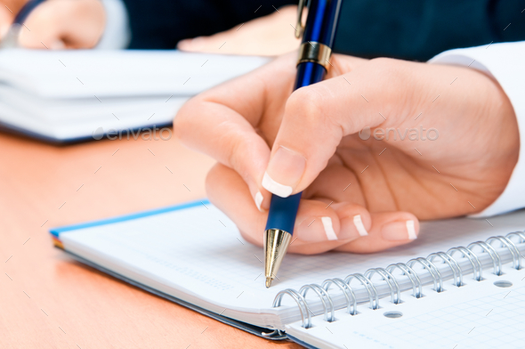 Cropped image of hand of young woman taking notes - Stock Photo - Images