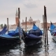 Gondolas on the Pier. Against the Cityscape of Venice