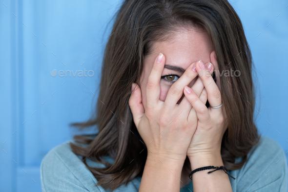 Studio shot of brunette girl hiding eyes under hand while feeling ashamed. - Stock Photo - Images