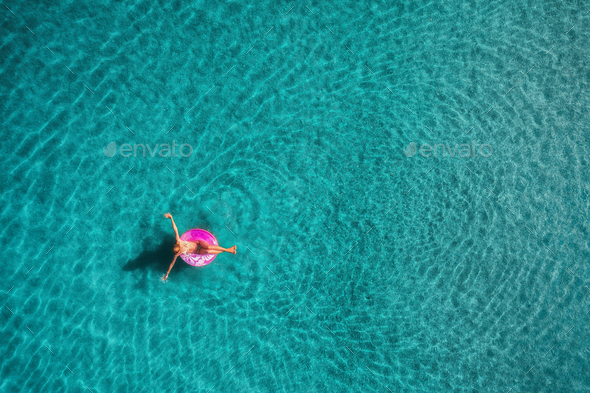 Aerial view of young woman swimming on the pink swim ring - Stock Photo - Images