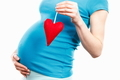 Pregnant woman with red heart, symbol of new life and expecting for baby