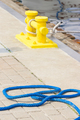 Blue rope and mooring bollard in background, detail of seaport, yachting concept