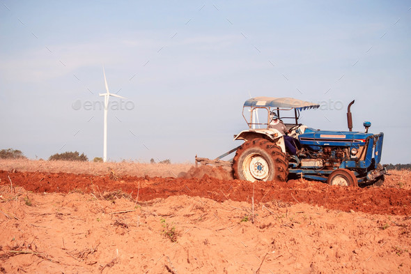 Farmers are using tractors to plow the soil