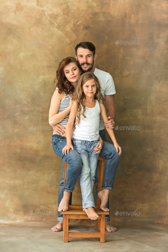 Pregnant mother with teen daughter and husband. Family studio portrait over brown background