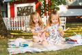 Two little girls sitting on green grass