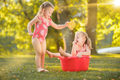The cute little blond girls playing with water splashes on the field in summer