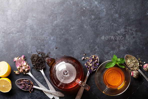 Tea cup, teapot and assortment of dry tea in spoons