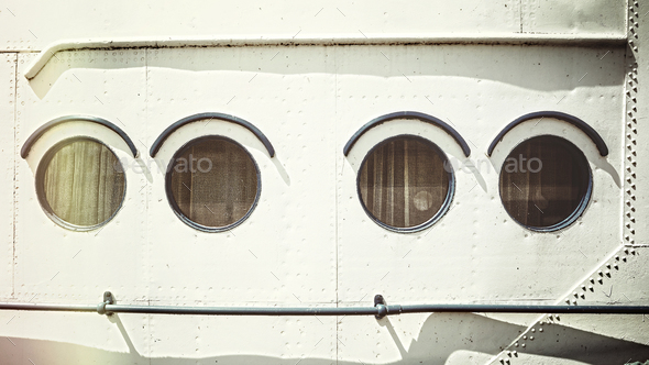 Retro stylized close up picture of an old ship portholes